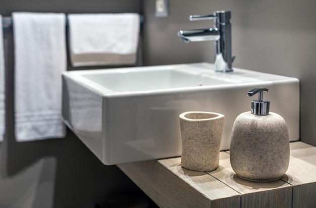 Foto superficial de uma pia moderna ao lado da garrafa no banheiro
