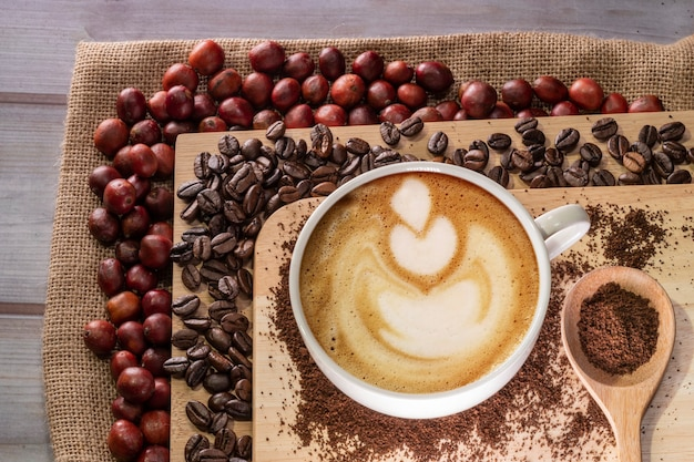 Foto superior de xícara de café com leite e grãos de café