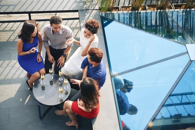 Foto superior do grupo de convidados da festa, sentados ao redor da mesa com bebidas no terraço ao ar livre