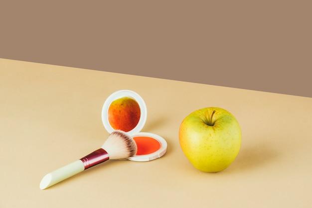 Foto surrealista de uma maçã refletida no espelho de um pó de maquiagem