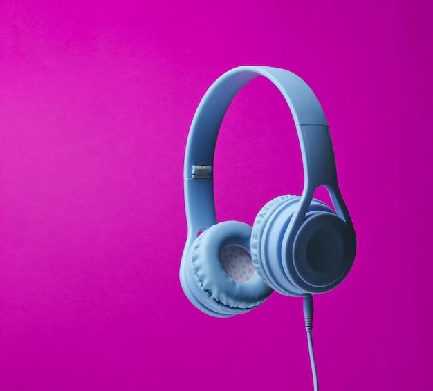 Foto surround 3d de fones de ouvido modernos em um fundo roxo