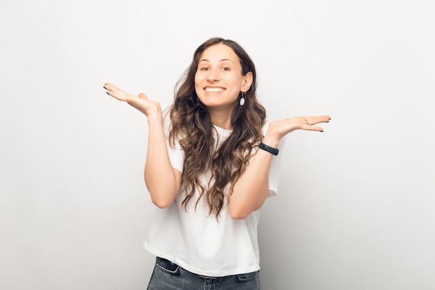 Foto temática de branco de uma jovem encolhendo os ombros ou fazendo o gesto surpresa com os braços.