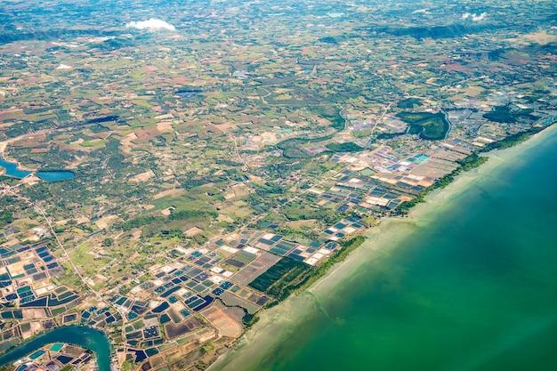Foto tirada do avião a jato que fotografou a ampla cidade ao lado da praia e do mar no meio da tailândia.