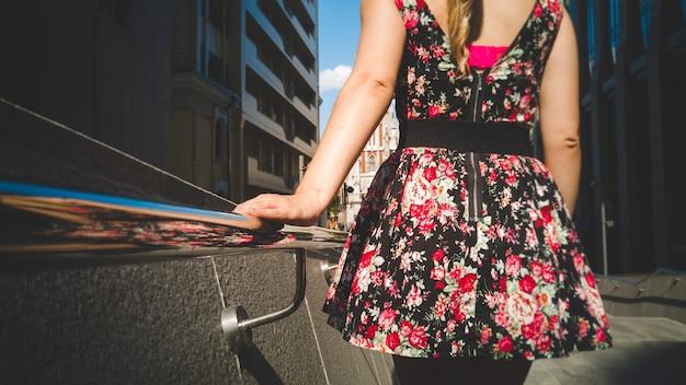 Foto tonificada de mulher jovem e bonita em um vestido curto com estampa floral descendo as escadas em stret e segurando as mãos em corrimãos de metal