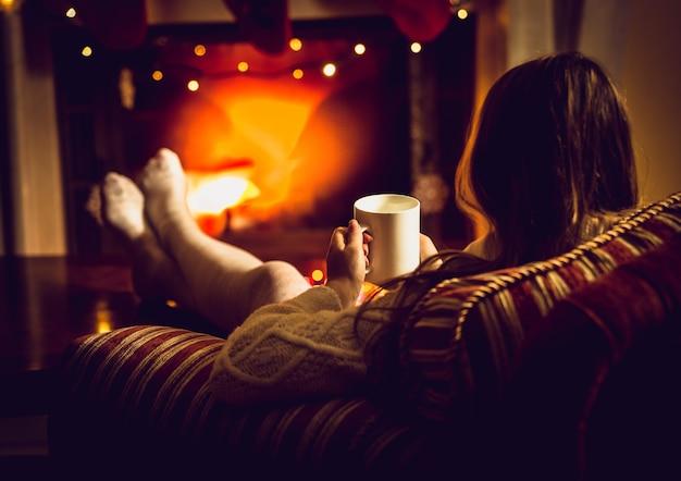 Foto tonificada de mulher se aquecendo com chá quente na lareira no inverno