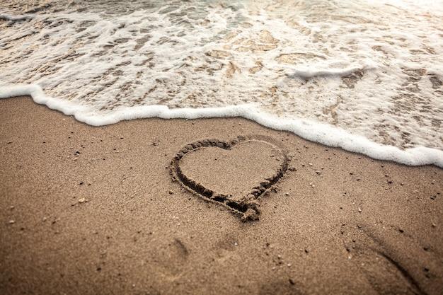 Foto tonificada de um coração desenhado na areia sendo lavado pela onda do mar