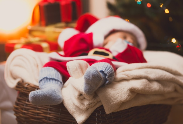 Foto tonificada de um lindo bebê papai noel deitado em meias de malha azuis