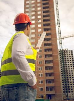 Foto tonificada do engenheiro de construção apontando para um prédio em construção