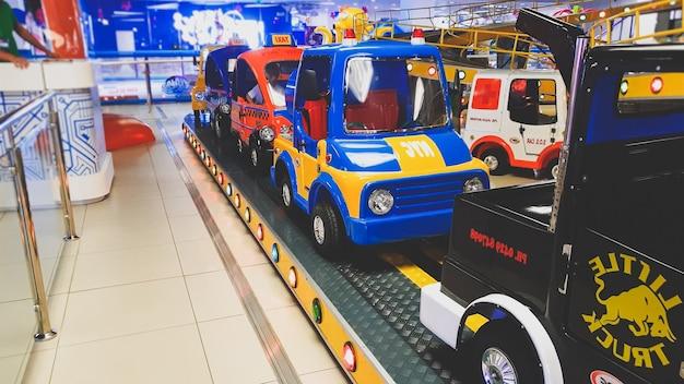 Foto tonificada em close de um trem colorido com carrinho parecendo carros para crianças no parque temático de diversões