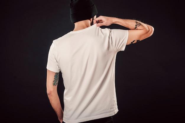 Foto traseira de um homem barbudo bonito com corte de cabelo fresco e braços tatuados posando em uma maquete de parede isolada em uma camiseta branca simples em branco pronta para desenhos