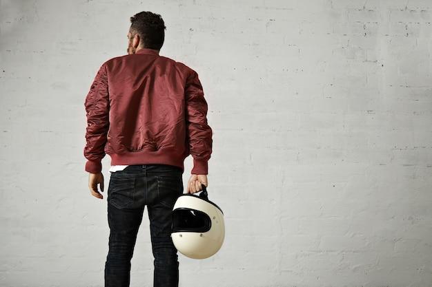 Foto traseira de um piloto barbudo em uma jaqueta bomber de náilon vermelho bordô, jeans skinny estressados e com um capacete branco em branco na mão em um estúdio com parede de tijolos brancos