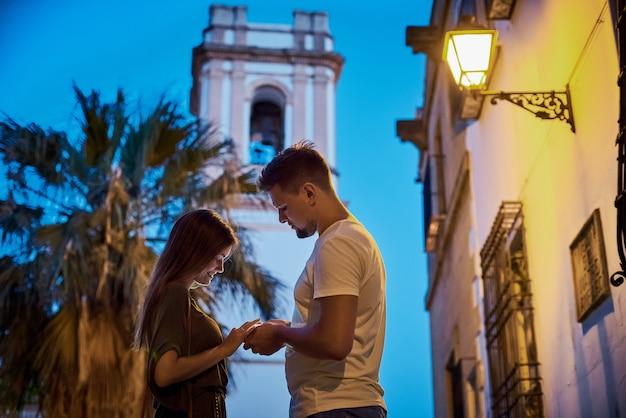 Foto urbana do jovem casal adulto olhando para celular