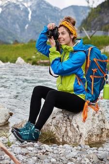 Foto vertical ao ar livre de mulher alegre faz fotos profissionais, sentada nas rochas perto do rio da montanha