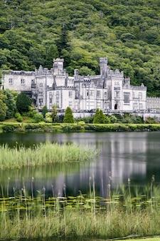 Foto vertical da abadia de kylemore na irlanda, cercada por vegetação e um lago