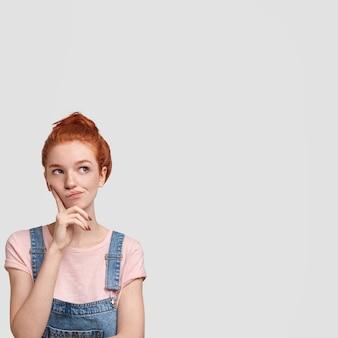 Foto vertical da adorável mulher ruiva perdida em pensamentos