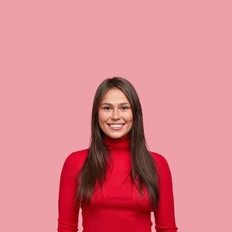 Foto vertical da bela jovem arquiteta com um sorriso brilhante e uma covinha na bochecha