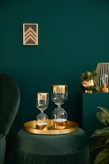 Foto vertical da elegante sala de estar com pufe de veludo verde, decoração dourada, ampulheta de design, moldura na parede e acessórios elegantes. elemento do interior luxuoso em uma casa aconchegante.