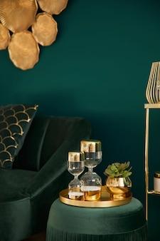 Foto vertical da elegante sala de estar com pufe de veludo verde, decoração dourada, ampulheta de design, sofá e acessórios elegantes. elemento do interior luxuoso em uma casa aconchegante. modelo.