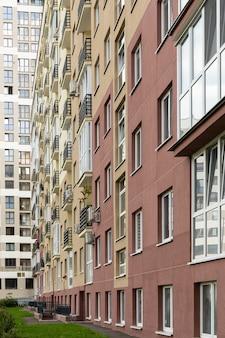 Foto vertical da fachada moderna de alta construção nova, grama no chão