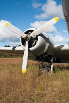 Foto vertical da hélice de um avião pousando na grama seca