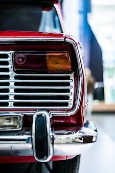 Foto vertical da parte traseira de um carro vermelho clássico vintage