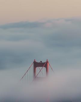 Foto vertical da ponte golden gate cercada por nuvens