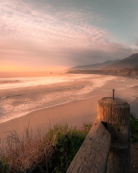 Foto vertical da praia durante o pôr do sol