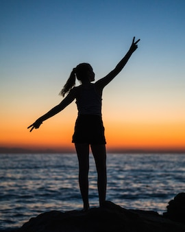 Foto vertical da silhueta de uma mulher com os braços abertos mostrando o sinal da vitória