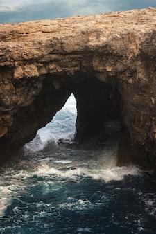 Foto vertical das águas do oceano sob um penhasco