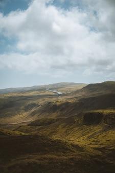 Foto vertical das belas colinas cobertas de grama sob o céu nublado, capturada na islândia