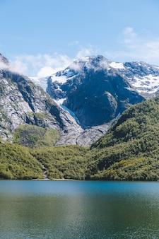 Foto vertical das belas montanhas à beira do oceano calmo, capturada na noruega