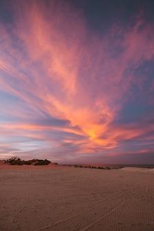 Foto vertical das colinas arenosas sob o céu colorido de tirar o fôlego, capturada no norte do brasil