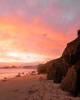 Foto vertical das montanhas na praia durante o pôr do sol