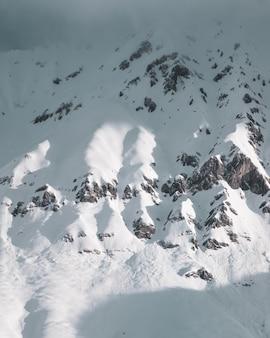 Foto vertical das montanhas rochosas cobertas de neve