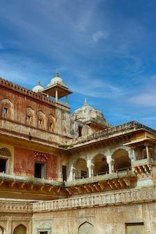 Foto vertical das muralhas do forte amber sob um céu azul e luz do sol na índia