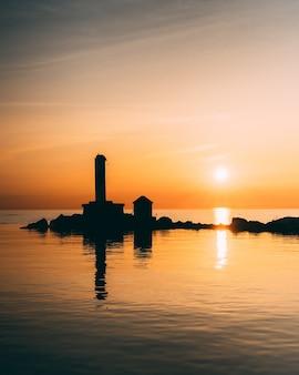 Foto vertical das silhuetas dos edifícios no meio de um oceano calmo durante o pôr do sol