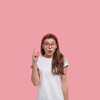 Foto vertical de adolescente bonita espantada aponta com o dedo indicador para cima, diz