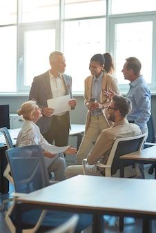 Foto vertical de alegres executivos multirraciais em uma reunião no escritório moderno