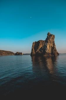 Foto vertical de algumas pedras grandes no mar