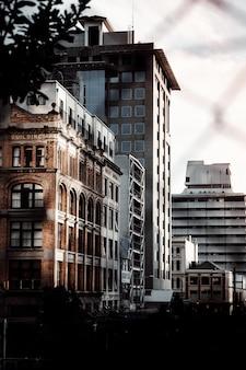 Foto vertical de alguns belos edifícios capturados através de algumas cercas