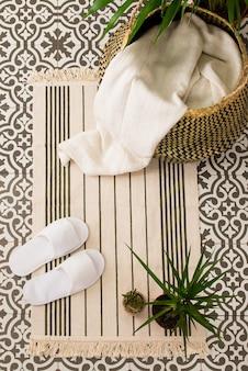 Foto vertical de alto ângulo de chinelos em um pequeno tapete no chão perto de uma cesta e plantas caseiras