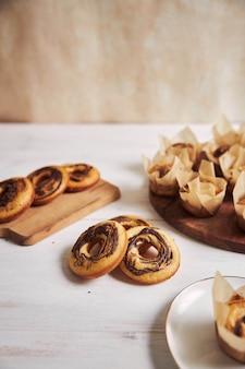 Foto vertical de alto ângulo de deliciosos muffins de chocolate e donuts em uma mesa branca