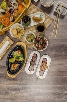 Foto vertical de alto ângulo de diferentes pratos asiáticos em uma mesa de madeira