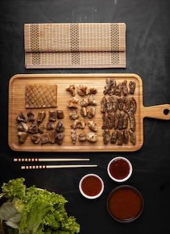 Foto vertical de alto ângulo de pedaços de carne assada em uma bandeja com pauzinhos e molhos na mesa