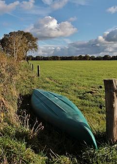 Foto vertical de alto ângulo de um barco verde virado de cabeça para baixo em um vale verde