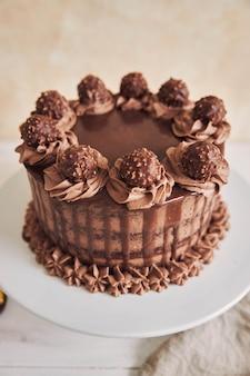 Foto vertical de alto ângulo de um bolo de chocolate fresco decorado com um delicioso chocolate em um prato