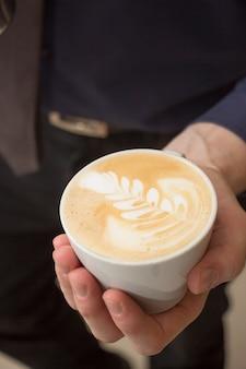 Foto vertical de alto ângulo de um homem segurando uma xícara de cappuccino