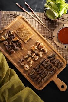 Foto vertical de alto ângulo de um prato de madeira cheio de comida assada em uma superfície preta