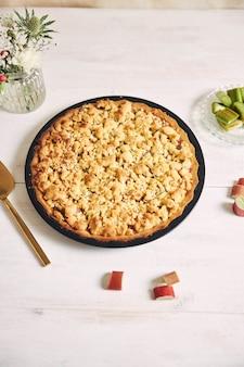 Foto vertical de alto ângulo de um prato de torta de bolo rhabarbar crocante e alguns ingredientes em uma mesa