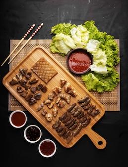 Foto vertical de alto ângulo de uma bandeja de carne frita, batatas, molho e vegetais